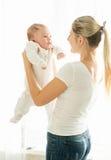 Портрет усмехаясь матери прижимаясь она 3 месяца старого младенца Стоковые Фотографии RF