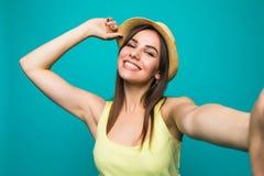 Портрет усмехаясь милой женщины делая фото selfie на smartphone изолированном на предпосылке цвета Стоковая Фотография RF