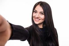 Портрет усмехаясь милой женщины делая фото selfie на smartphone изолированном на белой предпосылке Стоковые Изображения