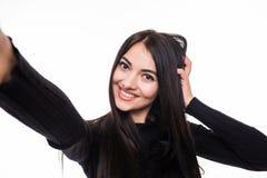 Портрет усмехаясь милой женщины делая фото selfie на smartphone изолированном на белой предпосылке Стоковое Изображение RF