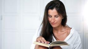 Портрет усмехаясь милой книги чтения женщины и поворачивая страницы сидя на кровати в спальне сток-видео