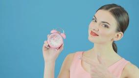 Портрет усмехаясь милого брюнет с розовыми часами в руке на голубой предпосылке в студии белизна времени предмета предпосылки изо видеоматериал