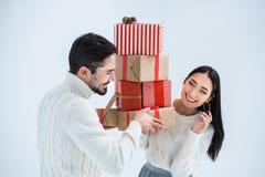 портрет усмехаясь многокультурных пар смотря один другого пока держащ стог обернутых подарков рождества Стоковые Изображения