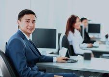 Портрет усмехаясь молодого бизнесмена работая на компьютере на офисе с его коллегами Стоковое Изображение