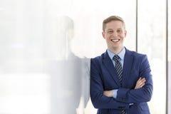 Портрет усмехаясь молодого бизнесмена с оружиями пересек полагаться на стене на офис стоковые изображения