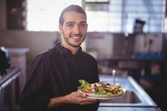 Портрет усмехаясь молодого кельнера держа плиту салата на коммерчески кухне Стоковые Фото