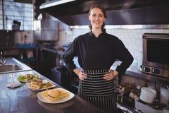 Портрет усмехаясь молодого кельнера стоя с руками на бедре едой Стоковая Фотография RF