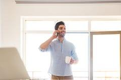 Портрет усмехаясь молодого человека говоря на мобильном телефоне Стоковые Изображения