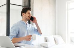 Портрет усмехаясь молодого человека говоря на мобильном телефоне Стоковые Фотографии RF
