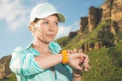 Портрет усмехаясь молодой девушки фитнеса в крышке и наушниках проверяя ее умные часы пока сидящ outdoors против стоковое изображение