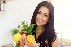 Портрет усмехаясь молодой домохозяйки в современной кухне стоковые фото