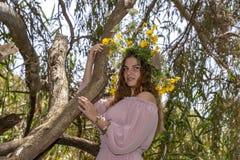 Портрет усмехаясь молодой женщины в венке цветков близких вверх по полагаться на стволе дерева стоковое изображение rf