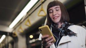 Портрет усмехаясь молодой женщины в наушниках ехать публично переход, слушает музыка и просматривающ на желтом смартфоне сток-видео