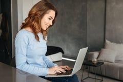 Портрет усмехаясь молодой женщины используя портативный компьютер Стоковая Фотография