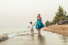 Портрет усмехаясь молодой матери при маленький ребенок бежать на th стоковая фотография