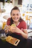 Портрет усмехаясь молодой шикарной женщины есть бургер на кофейне Стоковые Фото