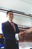 Портрет усмехаясь молодого азиатского предпринимателя людей тряся руки с его коллеги работы Стоковые Изображения