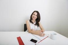 Портрет усмехаясь молодого сочинительства коммерсантки на связывателе на столе в офисе Стоковые Фотографии RF