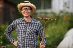 Портрет усмехаясь молодого человека садовника держа грабл outdoors Стоковая Фотография RF