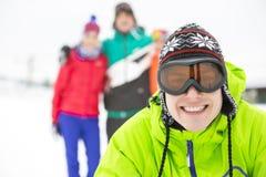 Портрет усмехаясь молодого человека с друзьями в предпосылке во время зимы Стоковые Изображения RF