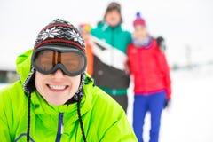 Портрет усмехаясь молодого человека с друзьями в предпосылке во время зимы Стоковое Фото