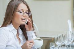Портрет усмехаясь молодой женщины говоря на клетке Стоковые Фото