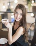 Портрет усмехаясь молодой женщины имея кофе на кафе Стоковые Изображения RF