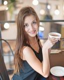 Портрет усмехаясь молодой женщины имея кофе на кафе Стоковые Изображения