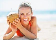 Портрет усмехаясь молодой женщины на пляже держа кокос стоковое фото rf