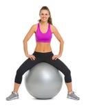 Портрет усмехаясь молодой женщины пригодности на шарике пригодности стоковая фотография