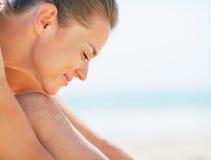 Портрет усмехаясь молодой женщины сидя на пляже Стоковые Изображения