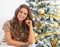 Портрет усмехаясь молодой женщины сидя около рождественской елки Стоковые Фотографии RF