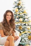 Портрет усмехаясь молодой женщины сидя около рождественской елки Стоковое Фото