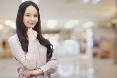 Портрет усмехаясь молодой женщины с длинними волосами и рукой на ее подбородке, внутри помещения Стоковая Фотография