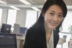 Портрет усмехаясь молодой коммерсантки в офисе Стоковые Изображения RF