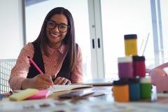 Портрет усмехаясь молодой коммерсантки работая на офисе Стоковая Фотография
