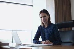 Портрет усмехаясь молодой коммерсантки с компьтер-книжкой на столе в офисе Стоковое Изображение