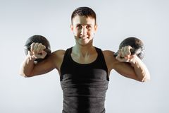 Портрет усмехаясь мышечного человека выполняя тренировки с весами стоковое фото rf