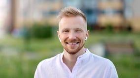 Портрет усмехаясь наушников bluetooth случайного молодого европейского человека нося беспроводных видеоматериал