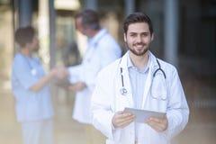 Портрет усмехаясь доктора стоя с цифровой таблеткой Стоковые Изображения
