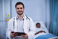 Портрет усмехаясь доктора стоя с цифровой таблеткой Стоковое Изображение