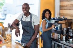 Портрет усмехаясь официантки и кельнера работая на счетчике Стоковая Фотография