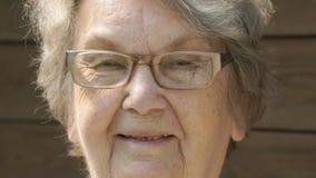 Портрет усмехаясь пожилой женщины в стеклах сток-видео
