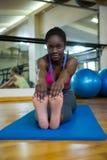 Портрет усмехаясь подходящей женщины делая протягивающ тренировку на циновке Стоковое Изображение