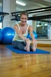 Портрет усмехаясь подходящей женщины делая протягивающ тренировку на циновке Стоковое Фото