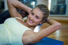 Портрет усмехаясь подходящей женщины делая протягивающ тренировку на циновке Стоковое Изображение RF