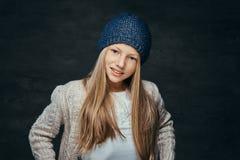 Портрет усмехаясь предназначенной для подростков девушки со светлыми волосами нося шляпу и свитер зимы стоковое изображение rf