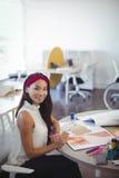 Портрет усмехаясь предпринимателя работая в творческом офисе Стоковое фото RF
