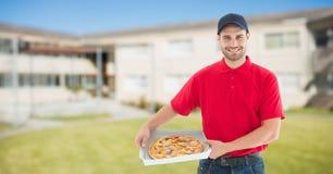Портрет усмехаясь работника доставляющего покупки на дом держа коробки пиццы против зданий Стоковая Фотография RF