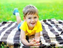 Портрет усмехаясь ребенка мальчика лежа на траве Стоковое фото RF